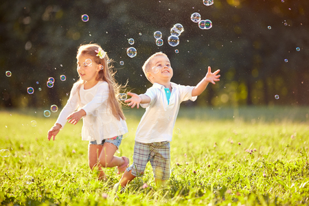 Photo pour Cheerful children run and chase bubbles in nature - image libre de droit