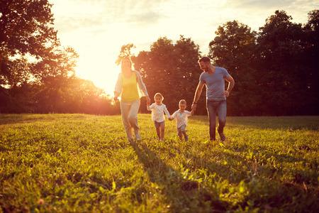 Photo pour Happy young children with parents running in park - image libre de droit