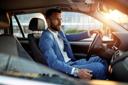 Foto de Attractive elegant man in business suit driving car - Imagen libre de derechos