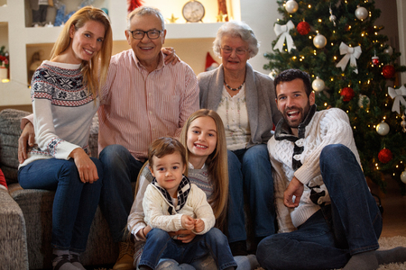 Foto de Smiling grandpa and grandma with children enjoy for Christmas - Imagen libre de derechos
