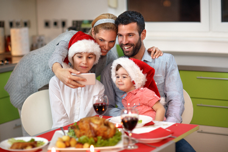 Photo for Family with children making Christmas selfie together at the table with food - Royalty Free Image