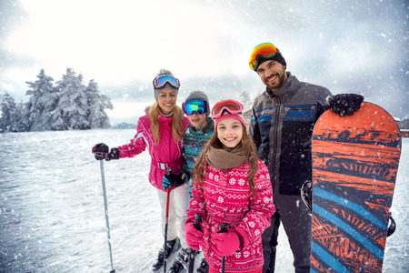 smiling family enjoying winter sports and vacation on snow in mountains