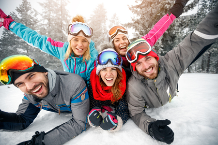 Foto de Group of skiers male and female enjoying together on snow in mountain  - Imagen libre de derechos