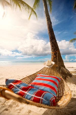 Foto de Romantic hammock in the shadow of the palm on the tropical beach by the sea - Imagen libre de derechos