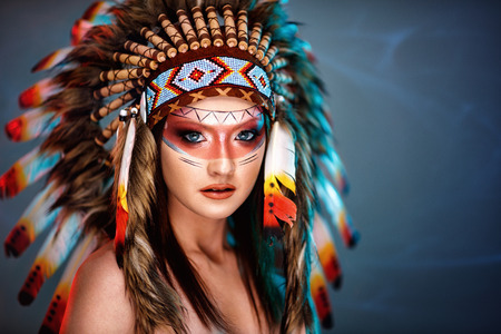Photo pour Beautiful young woman with big American Indian plume of feathers background - image libre de droit