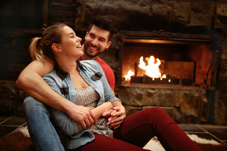 Photo pour Happy hugging couple enjoying in mountain house near fire from fireplace - image libre de droit
