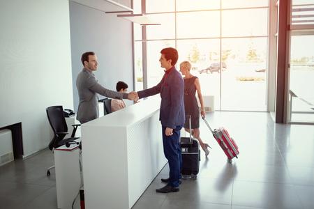 Photo pour Young business people arriving at the hotel reception - image libre de droit