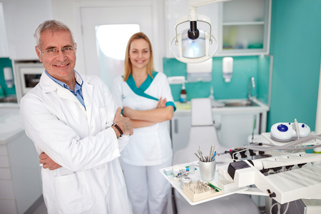 Foto de Portrait of senior dentist with nice female assistant in dental practice - Imagen libre de derechos