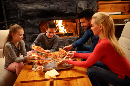 Photo pour Happy family eating pizza together  for dinner - image libre de droit