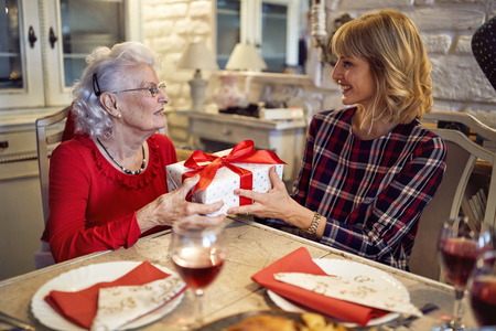 Photo pour Smiling daughter and senior mother m together celebrate Christmas at home - image libre de droit