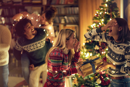 Happy girl surprising her friend girl with a romantic present at Christmas. Concept of celebration Christmas and new year.
