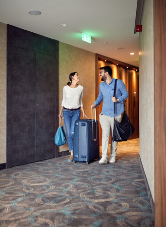 Photo for Smiling man and woman arriving at hotel lobby with suitcase - Royalty Free Image