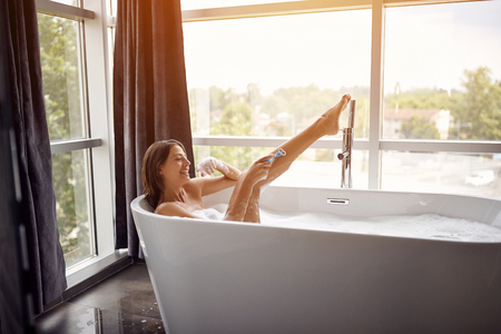 Photo for Young happy girl shaving her legs in the bath with foam - Royalty Free Image