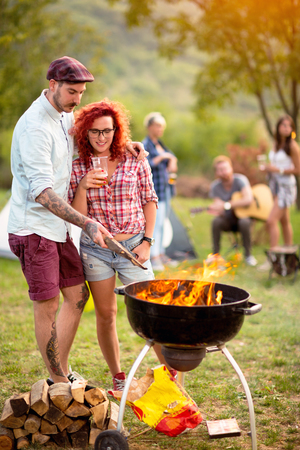 Photo pour Curly ginger girl with tattooed guy look at grill fire in camp in nature - image libre de droit