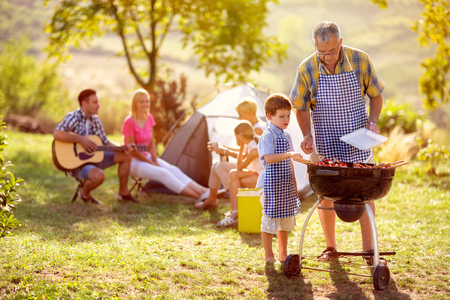 Photo pour grandson cooking on campfire with grandfather on camping - image libre de droit