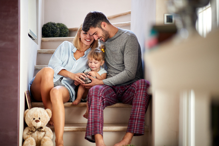 Photo pour Mom and dad with adorable kid having fun on stairs - image libre de droit