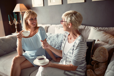 Photo pour Young female with mother talking and drinking coffee - image libre de droit