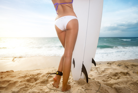 Photo for Back view of surfer woman  holding a surfboard - Royalty Free Image