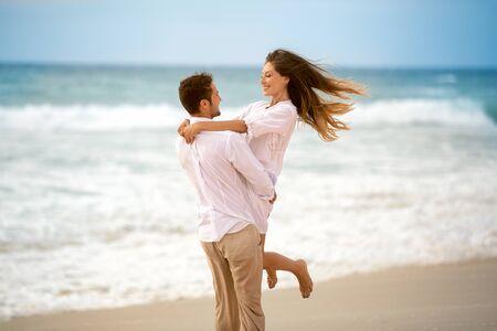 Foto de Romantic lovers on beach,  man holding his girlfriend and are running in circles - Imagen libre de derechos