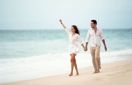 Photo pour Couple walking on beach. Young happy couple walking on beach smiling holding hands - image libre de droit