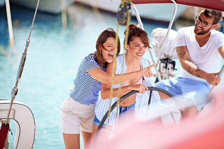 Photo pour Happy friends on a sailboat at wheel going on ocean trip at summer holiday - image libre de droit