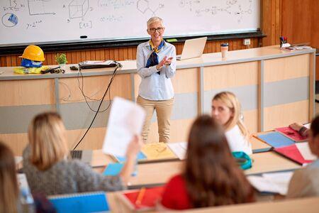 Foto de female lecturer with students in an exam in a classroom - Imagen libre de derechos