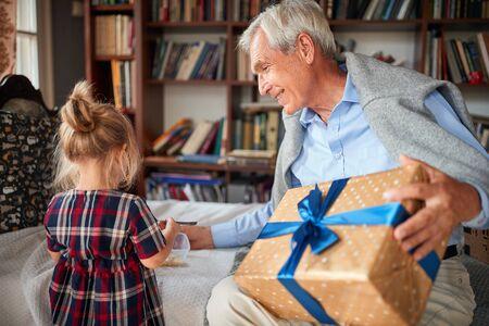 Photo pour Smiling grandfather celebration Christmas time with his little granddaughter - image libre de droit