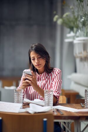 Photo pour young girl  sitting at cafe eat and looking at mobile phone. - image libre de droit