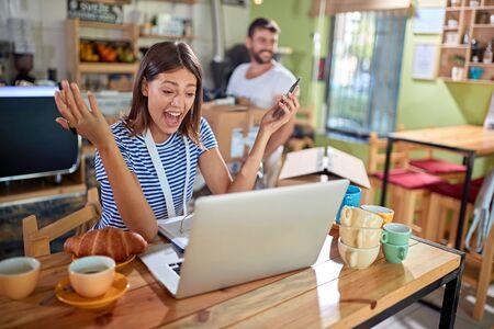 Photo pour Smiling  woman with laptop looking ideas for a new cafe. - image libre de droit