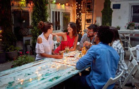Foto de Young friends enjoy friendly conversation at dusk at cafe's garden - Imagen libre de derechos