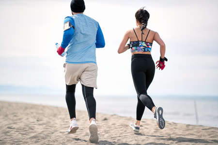 Photo pour Fitness young man and woman  running along beach together. - image libre de droit