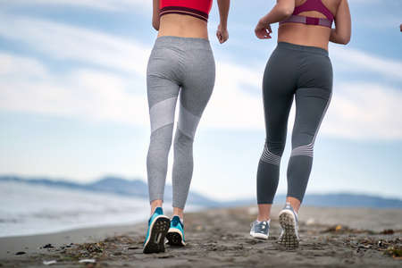 Photo for Two women jogging together on the beach - Royalty Free Image