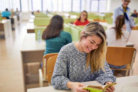 Photo pour Female student enjoys reading the literature at the lecture in the university classroom - image libre de droit