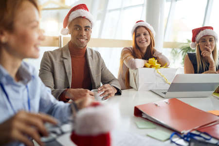 Photo pour workers looking at their boss with smile wearing santa hats, smiling - image libre de droit