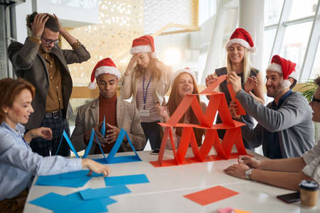 Foto de multiethnic group colleagues building paper towers at work in the office for christmas, playing - Imagen libre de derechos