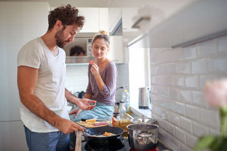 Foto de A young couple in love enjoying preparing breakfast together on a beautiful morning in the kitchen. Cooking, together, kitchen, relationship - Imagen libre de derechos
