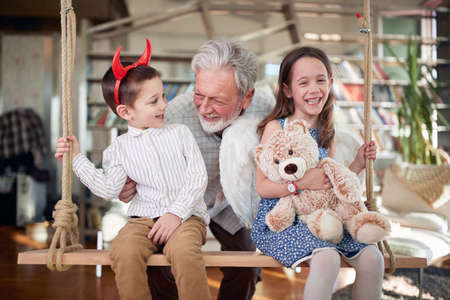 Photo pour Grandpa spending enjoys chatting with grandchildren sitting on the swing in a cheerful atmosphere at home. Family, leisure, together - image libre de droit