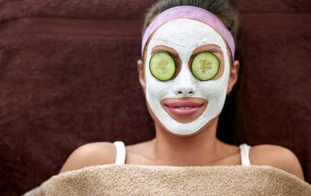 Photo pour Smiling woman with cosmetic mask and cucumber on eyes, regeneration - image libre de droit