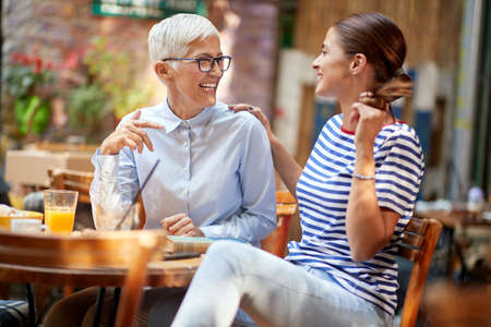 Photo pour Two female friends of different generations have a friendly talk while they have a drink in a pleasant atmosphere in the bar. Leisure, bar, friendship, outdoor - image libre de droit