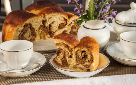 Typical italian flavorous home baked cake La Gubana with sophisticated stuffing (hazelnuts, fruit, chocolate, walnut, raisins, honey etc.) with purple flowers of salvia on the table covered for breakfast. Traditionally bake for Christmas and Easter.
