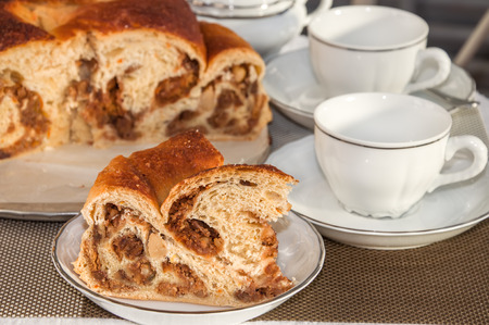 Good piece of typical italian flavorous home baked cake La Gubana with sophisticated stuffing (hazelnuts, fruit, chocolate, walnut, raisins, honey etc.) on the table covered for tea time. Traditionally bake for Christmas and Easter.