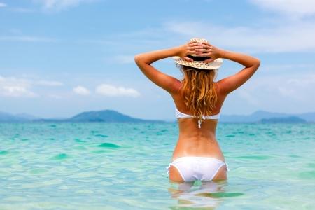 Foto de Beautiful young woman in bikini on the sunny tropical beach relaxing in water - Imagen libre de derechos