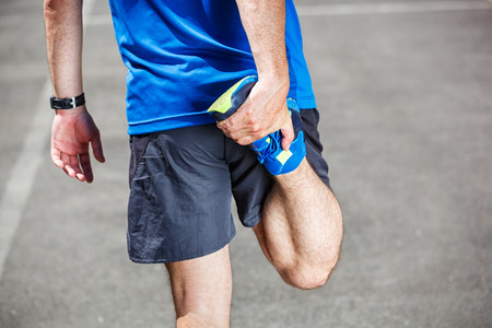 Male runner stretching before workout.