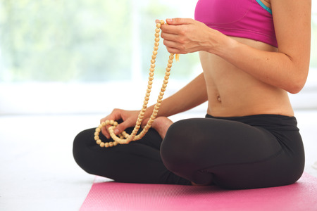 Young beautiful woman meditating in lotus pose.