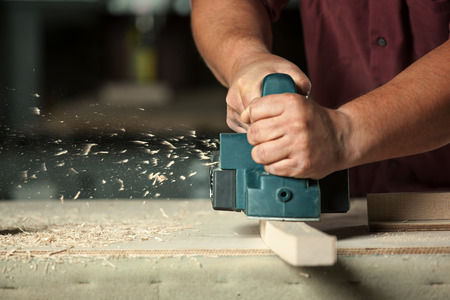 Carpenter working with electric planer on wooden plank in workshop.