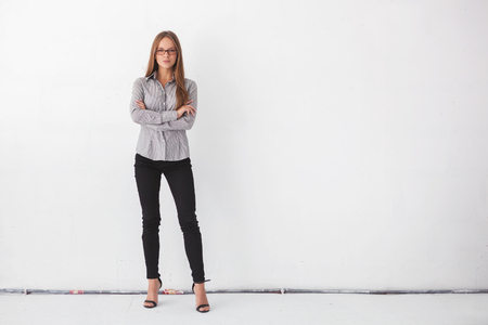 Portrait of young beautiful business woman standing against white wall.