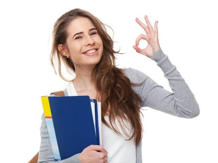 Foto de Young happy student showing ok sign isolated on white background. - Imagen libre de derechos