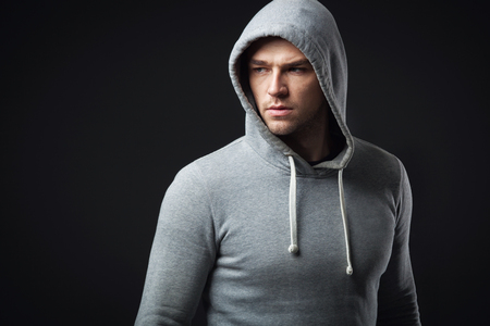 Studio portrait of cool looking young guy in sportswear.