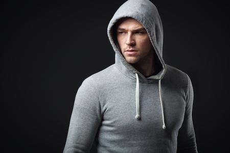 Studio portrait of cool looking young guy in sportswear.