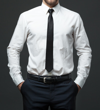 Photo pour Midsection of fit young businessman standing in formal white shirt, black tie and pants. - image libre de droit